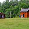 Visitors at the smokehouse and log cabin