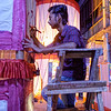 An artist putting the finishing touches on his neighborhood pandal.