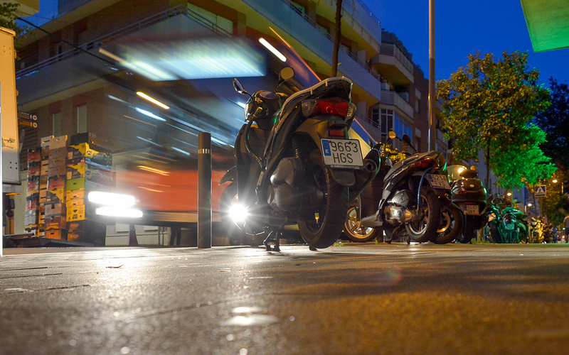 """For me, the focus of this scene was the large and loud bus racing down a residential street in Barcelona but the long exposure renders the image streaky so the bus is hard to recognize. Some of the """"preview"""" kids were drawn to the motorcycles and created a storyline about Elliott riding motorcycles. Elliott could be frightened by the noise or calmly waiting to board. I've always thought of Elliott as very brave and resourceful so assume he has a boarding pass and regularly takes the bus downtown."""