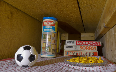 This photo was taken in a cupboard down in the basement of our house in Northampton. This is, presumably, the soft, warm and quiet place where Elliott rests during the day. The games, toy soccer ball and crystal saucer of Goldfish crackers are things that might entertain Elliott and the family.