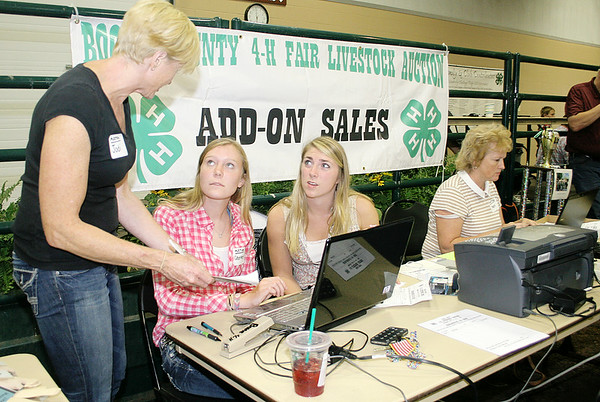 Rod Rose The Lebanon Reporter<br /> Jodi Gietl (left) explains to Courtney Gietl and MacKenzie Orbaugh how to record an entry during the Boone County 4-H Livestock Auction Thursday; Mary Hatton, far right, was one of the dozens of volunteers who kept the auction flowing smoothly.