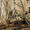 In 1987 I got permission to set up a homebase Tipi-lodge on 40 acres ten miles outside of Boone in Sugar Grove, NC.  I built several Tipis on this ridgetop location and cut a switchbacked trail to the top of the mountain from the land's closest road access about a mile away.  The trail was contoured because it had to gain around a thousand feet of elevation and so everything was backpacked up the mountain.<br /> <br /> This early Tipi is covered with old chestnut tree sides found in the woods, and the outside perimeter is fenced with cordage to hold a couple feet of insulating dead leaves and renewed each October after the leaves fell.  My water spring was a seep I discovered and dug out to place a pipe for retrieval.  It's down the hillside about a hundred yards and 200 lower in elevation.