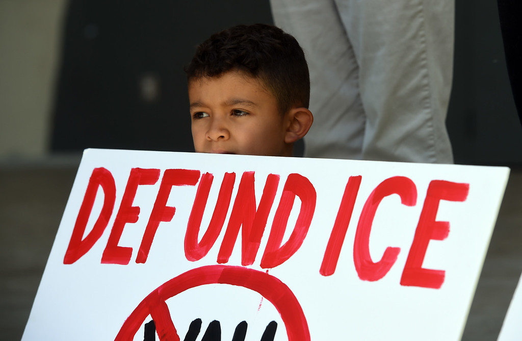 . Marcos Cordero, 7, takes his protest sign on stage during the rally. About  200 people protested in Central Park in Boulder on Friday about the Trump separation policy at the border with Mexico. For more photos, go to dailycamera.com. Cliff Grassmick  Staff Photographer  June 22, 2018