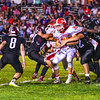North Middlesex quarterback Joe Haskins is held on by Groton-Dunstable's David Kimetto and a host of Crusader defenders. Nashoba Valley Voice/Ed Niser