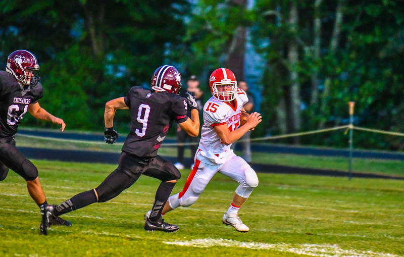 North Middlesex quarterback Joe Haskins looks to the sideline as Groton-Dunstable's Shamus Gelinas is in pursuit. Nashoba Valley Voice/Ed Niser