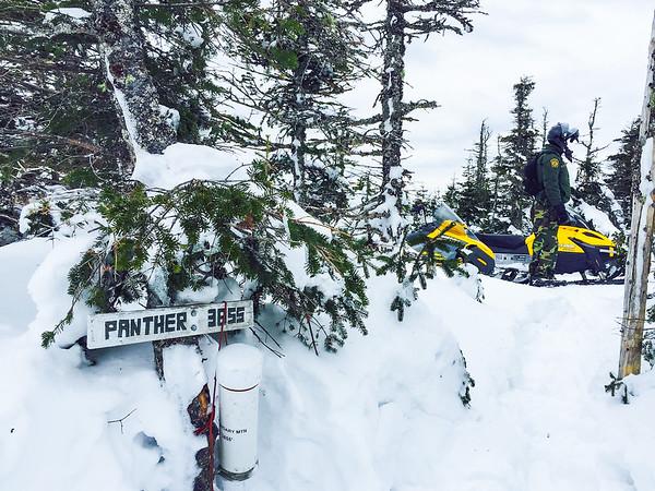 Border Patrol agent at Boundary Peak during snowmobile patrol