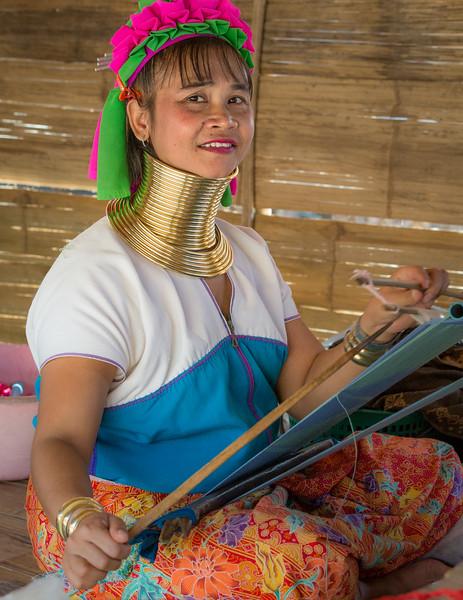 Ban Mae Khao Tom, Chiang Rai Province, Thailand. A Padaung Karen woman works at a loom. Padaung women produce beautiful fabrics and clothes made from them.