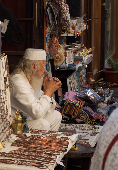 Man selling tourist wares in Mostar.