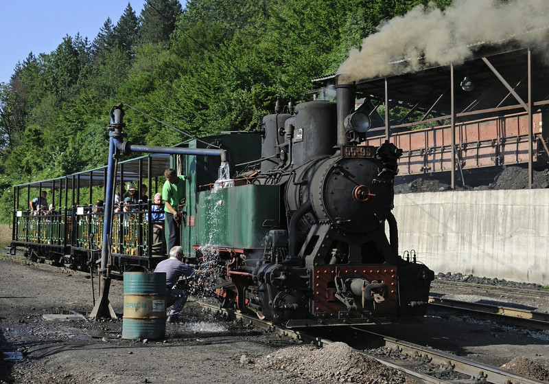 55-99, Oskova, Bosnia-Hercegovina, Tues 10 June 2014 1.  Taking water before the first of our three charters on the 76cm gauge line.  NB the the rather Disneyesque coaches, and the  coaling stage at right.