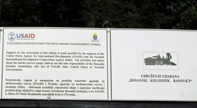 Overseas aid, Oskova, Bosnia-Hercegovina, Tues 10 June 2014.  Sign carried by the coaches provided for our first charter.  Our subsequent charters had stock more fitting to a colliery railway.