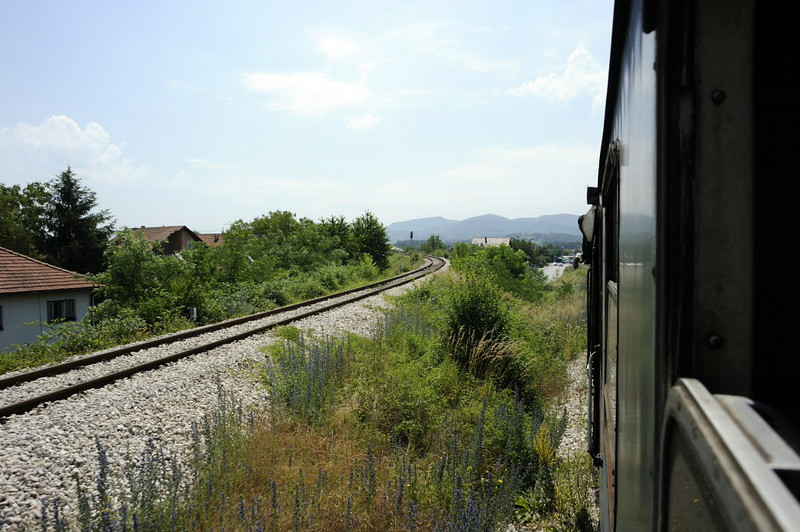 Leaving Zivinice, Bosnia-Hercegovina, Wed 11 June 2014 - 1125.  Heading south at Golubinjak before turning west to Banovici.  The line at left is the branch to Durdevik.