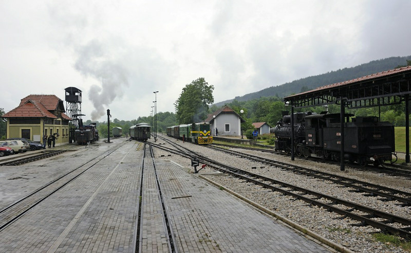 Sargan Vitasi station, Serbia, Sun 15 June 2014 2.  83-052 is taking water at left, alongside the stock of its charter train.  Serbian Rlys (SZ) 740-101 is about to leave with the service train to Mokra Gora.  83-173 is out of use at right.