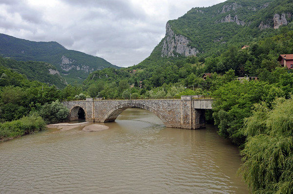 Disused railway bridge, Ustipraca, Bosnia-Hercegovina, Sat 14 June 2014.  Looking north.  The bridge used to carry a branch from Foca to Ustipraca (right), opened in 1939 in Yugoslav times.  The branch was extended to Miljevina in 1952.  At Ustipraca the branch joined the Austro-Hungarian Ostbahn (Eastern Rly) from Sarajevo to Visegrad and the Serbian border at Vardiste, opened in 1906.  The bridge crosses the River Praca at its confluence with the River Drina.  The water level has been raised since the bridge was built by a hydro-electric scheme on the Drina.