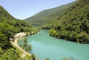 Soca (Isonzo) river, between Kanal ob Soci and Nova Gorica, Slovenia, 7 June 2014 - 1253.  Looking north east.  The emerald green river is 138km long.  It is best known by its Italian name, as it was the scene of ferocious fighting during the First World War.  In May 1915, Italy attacked its erstwhile ally Austria-Hungary, hoping that a short victorious war would lead to glory and territorial gains, particularly Trieste.  In fact, trench warfare, which already dominated the Western Front, soon developed on the Isonzo Front.  No fewer than 12 battles were fought on the hills along the Isonzo, including those seen in this and the next two photos.  After 11 battles and 30 months the Italians had suffered 300,000 dead and 740,000 wounded for very slight games.  They never reached Trieste.  The 12th battle, in October 1917, was an attack by Germany and Austria-Hungary,  It led to a total Italian rout in the disaster of Caporetto (Karfreit, now known as Kobarid).  The Italians were driven back 70 miles beyond their original front line.  They lost 10,000 dead, 30,000 wounded and 293,000 made prisoner.  More than 350,000 deserted.  But Italy had backed the winning side, and made substantial territorial gains in the 1919 peace settlement.  These included Trieste, which Italy retains to this day.