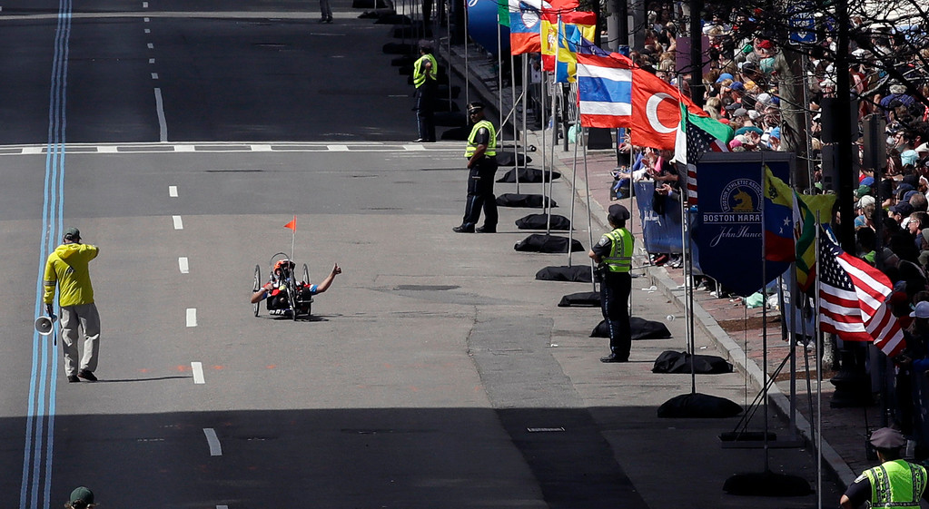 . Marc Fucarile, of Reading, Mass., gestures to spectators as he approaches the finish line in the men\'s handcycle division of the 121st Boston Marathon on Monday, April 17, 2017, in Boston. Fucarile lost a leg in the 2013 Boston Marathon bombing at this location. (AP Photo/Charles Krupa)