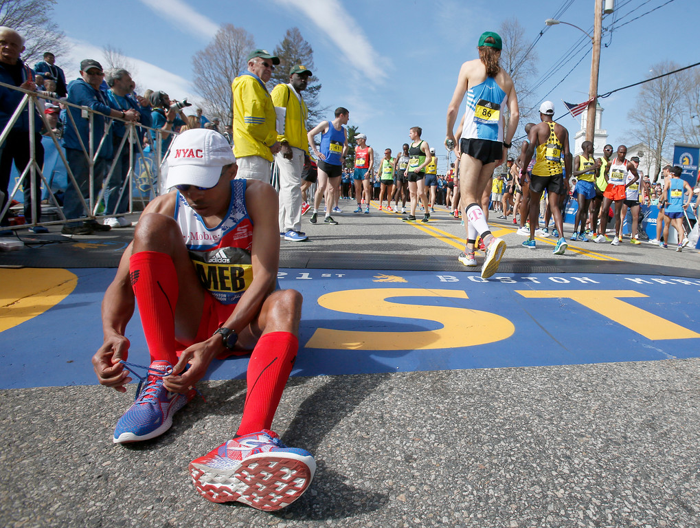 . Meb Keflezighi, of San Diego, sits at the start line as he ties his shoes before the start of the 2017 Boston Marathon in Hopkinton, Mass., Monday, April 17, 2017. (AP Photo/Mary Schwalm)