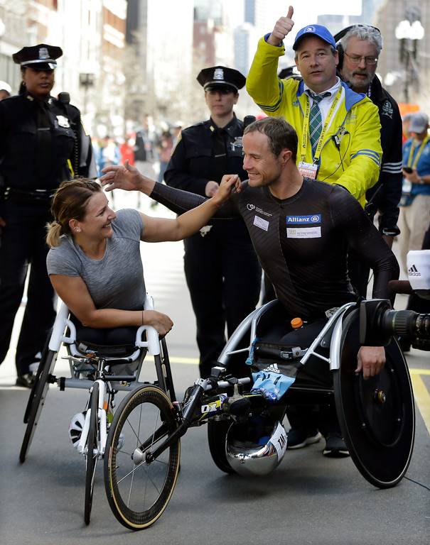 . Wheelchair division winners Manuela Schar, left, and Marcel Hug, both of Switzerland, celebrate their wins in the 121st Boston Marathon on Monday, April 17, 2017, in Boston. (AP Photo/Elise Amendola)