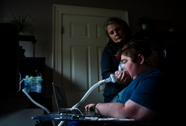 Christine McSherry helps her son Jett McSherry, who suffers from muscular dystrophy, with the Cough Assist machine to clear mucus from Jett's throat at their home in Pembroke, Massachusetts on April 22, 2017. For The Wall Street Journal.