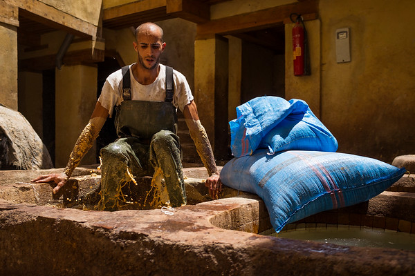 A worker softens hides in a white liquid by mixing the vat with his entire body before they can be dyed at the Chouara tannery in the Medina in Fes, Morocco.