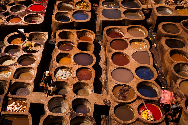 A worker carries vats of liquid between dying wells at the Chouara tannery in the Medina in Fes, Morocco.