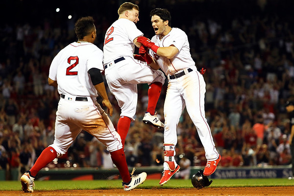 Andrew Benintendi #16 reacts with Brock Holt #12 and Xander Bogaerts #2 of the Boston Red Sox after hitting the game-winning walk-off single to defeat the New York Yankees in the tenth inning at Fenway Park on August 6, 2018 in Boston, Massachusetts.