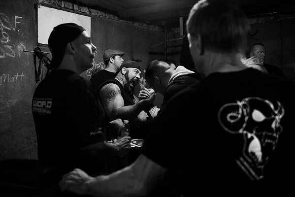 Devio watches other arm wrestler practice at Fitzsimmons basement.