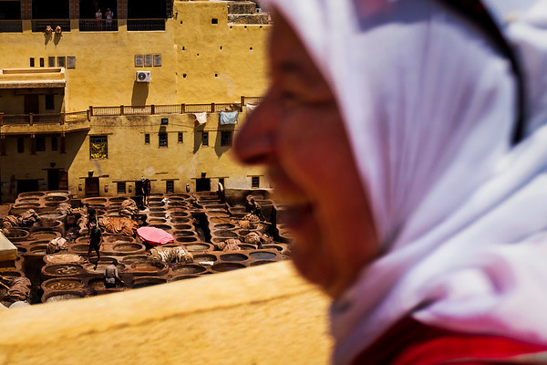 A woman looks on from the roof of a surrounding leather shop as workers operate inside the Chouara tannery below in the Medina in Fes, Morocco.