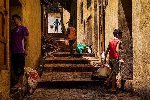 Workers and visitors stand in the entrance way to the Chouara tannery in the Medina in Fes, Morocco.