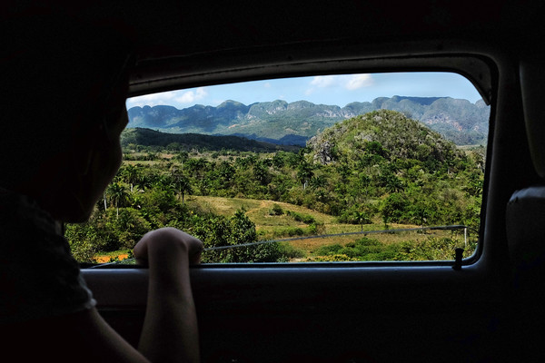 A woman admires the lush landscape of the Viñales Valley from the window of an old American car that has been transformed into a taxi.