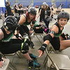 Boston Roller Derby at Shriners Auditorium. Bay State Punishers (black) vs Twin State Vixens (white). Punishers' Linda Marchiony of Hudson, MA (42), Sherry Thompson of Gardner (34) and Casey Van Vliet of West Boylston (421), reach for a water bottle for a teammate. (SUN/Julia Malakie)
