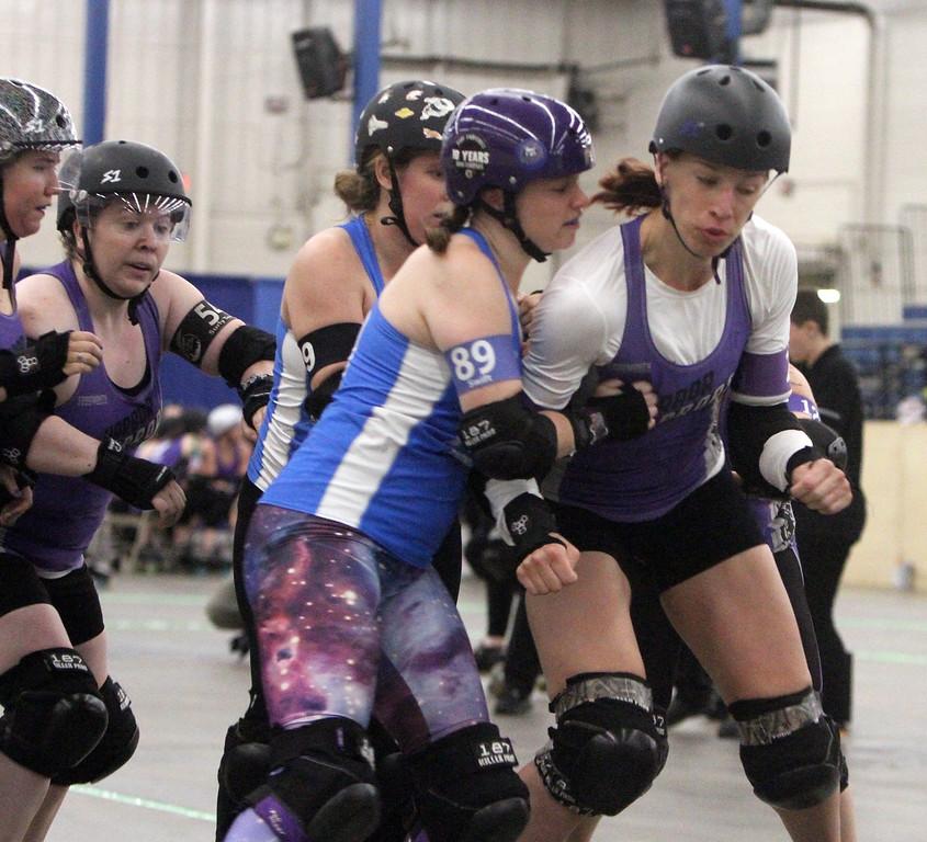 . Boston Roller Derby at Shriners Auditorium. Cosmonaughties (blue) vs Harbor Horrors (purple). Terror Swift (89), left, and Loch Tess Monstah (211), right. (SUN/Julia Malakie)