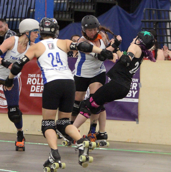 """Boston Roller Derby at Shriners Auditorium. Bay State Punishers (black) vs Twin State Vixens (white). Punishers' Allison Balik (24, """"Glutenless Maximus"""") of Somerville, formerly of Lowell, right, is knocked down by Vixens' Pumpkin Carvher (13). At left is Vixens' #23 (not on roster). (SUN/Julia Malakie)"""