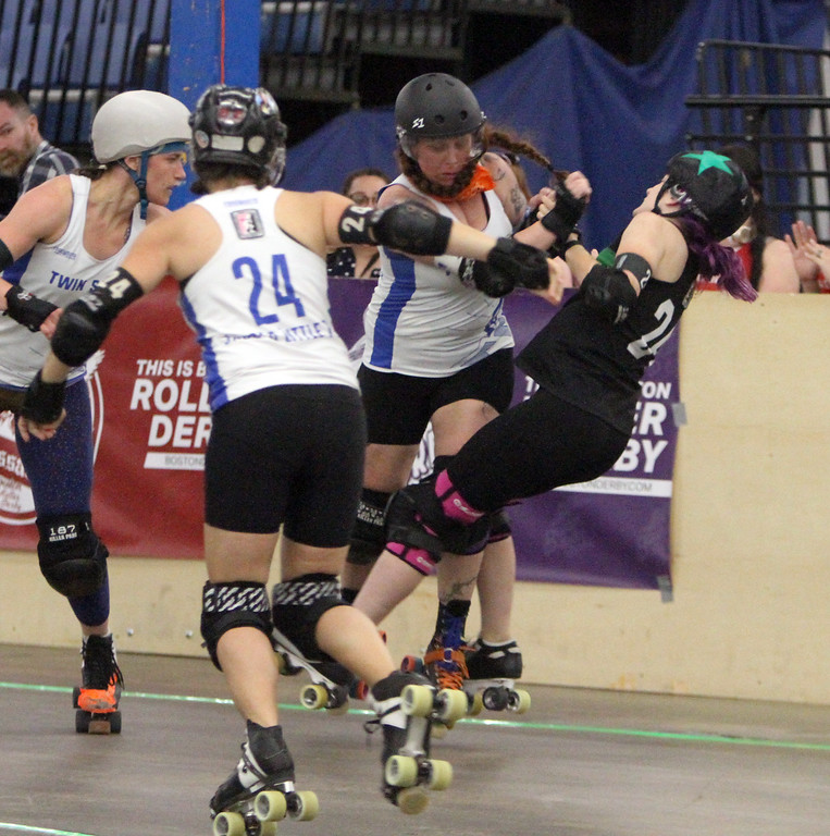""". Boston Roller Derby at Shriners Auditorium. Bay State Punishers (black) vs Twin State Vixens (white). Punishers\' Allison Balik (24, \""""Glutenless Maximus\"""") of Somerville, formerly of Lowell, right, is knocked down by Vixens\' Pumpkin Carvher (13). At left is Vixens\' #23 (not on roster). (SUN/Julia Malakie)"""