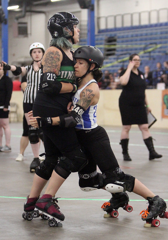 . Boston Roller Derby at Shriners Auditorium. Bay State Punishers (black) vs Twin State Vixens (white). Punishers\' Maggie Lavello of Worcester (213), and Vixens\' Midnight Crasher (2400). (SUN/Julia Malakie)