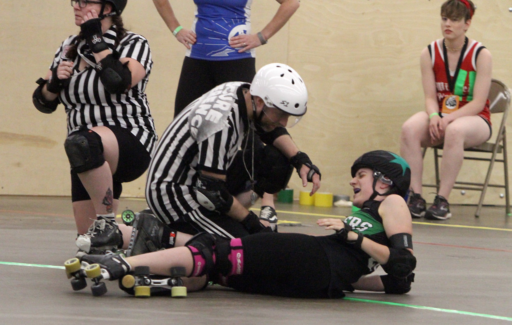 """. Boston Roller Derby at Shriners Auditorium. Bay State Punishers (black) vs Twin State Vixens (white). Referee checks on Punishers\' Allison Balik (24, \""""Glutenless Maximus\"""") of Somerville, formerly of Lowell. (SUN/Julia Malakie)"""