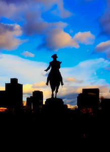 To Purchase  http://joann-vitali.artistwebsites.com/featured/2-george-washington-statue-boston-joann-vitali.html  A beautiful bright blue sky with orange and yellow tinted clouds make a stunning backdrop for the silhouette of the Boston Skyline and the George Washington Statue in the Boston Public Garden.   The statue is located near the Arlington street entrance that overlooks Commomwealth Avenue and the Back Bay neighborhood of Boston.