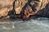 Himba-youth-in-pool-above-Epupa-falls,-Namibia