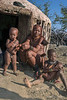 Himba-family-in-front-of-traditional-hut,-Epupa,-Namibia<br /> <br /> See how gently the little girl is holding the baby. The toddler appears to have an umbilical hernia