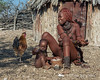 Himba-baby-spreading-his-maize-porridge-around,-Epupa,-Namibia<br /> <br /> I guess kids that age are the same everywhere - and the rooster was just hanging around hoping for some leftovers.