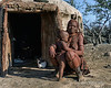Himba-mother-and-child-in-front-of-t aditional-mud-hut ,-Epupa,-Namibia