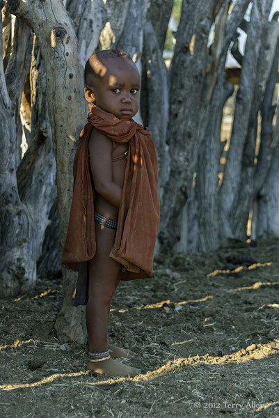 Himba-baby-lit-by-light-streaming-through-kraal-fence,-Epupa,-Namibia