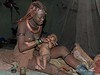 Himba-mother-with-very-young-baby-in-traditional-hut, -Epupa,-Namibia
