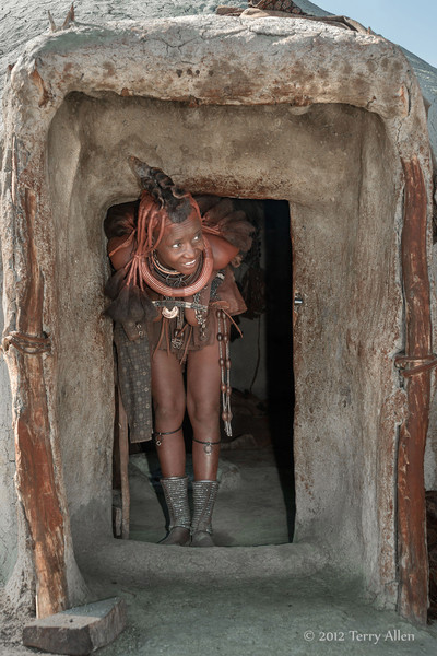 Himba-woman-peeking-out-of-her-hut,-Epupa-Namibia