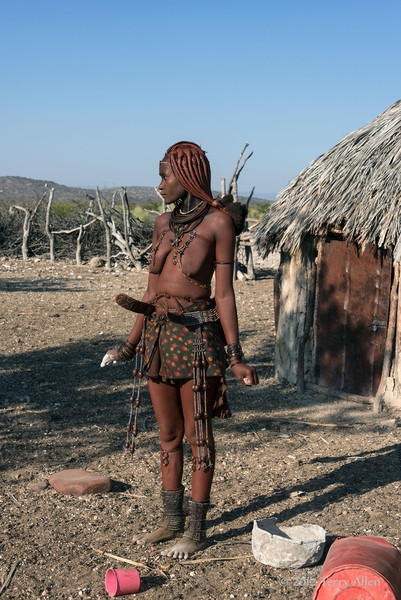 Himba-woman-in-front-of-traditional-hut-with-ash-container-for-making-otjize,-Epupa,-Namibia