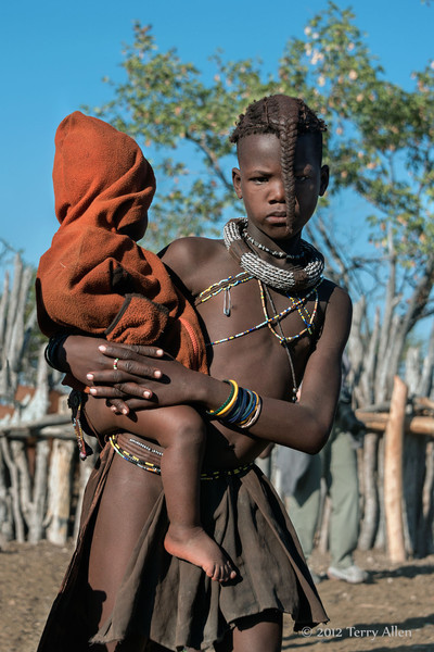 Himba-girl-carrying-her-little-brother,-Epupa,-Namibia