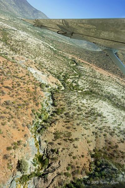 Rocky-terrain-reflected-in-plane-wing,-near-Epupa,-Namibia