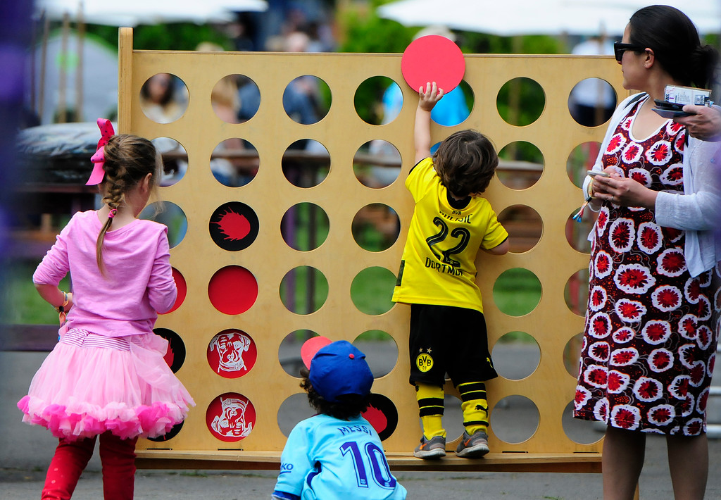 . NAPA, May 26- Xavier Cole, 2, of Petluma climbs to put in a chip in a Lagunitas connect four game during the second day of the BottleRock Napa Valley Music Festival. (Chris Riley/Times-Herald)