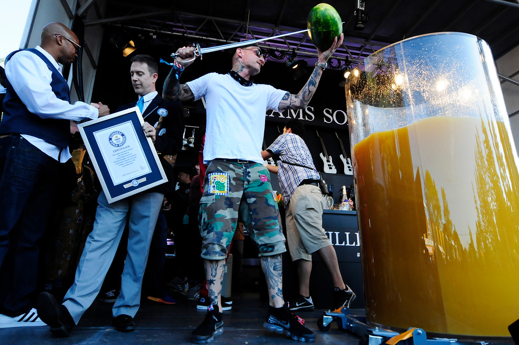 . NAPA, May 26- Michael Voltaggio spears a watermelon with a sword after breaking the world record for creating the largest gin and juice on the Williams Sonoma Culinary Stage on Saturday at BottleRock. (Chris Riley/Times-Herald)