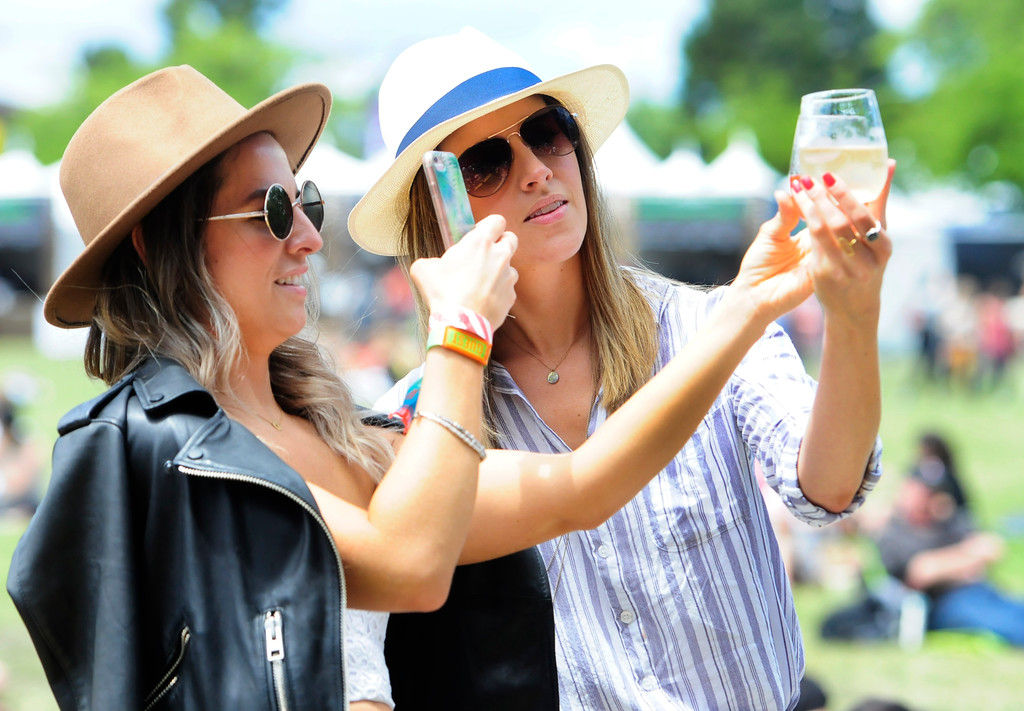 . NAPA, May 26-Leighann Smith, left, and Louise Houghton from Los Angeles take photos of their souvenir glasses as they wait for The Night Game perform on the Midway Stage during the second day of the BottleRock Napa Valley Music Festival.