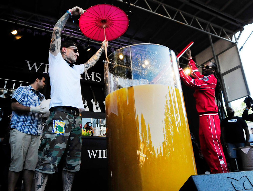 . NAPA, May 26- Snoop Dogg sticks a giant straw into the world record breaking largest gin and juice as Michael Voltaggio holds the umbrella on the Williams Sonoma Culinary Stage on Saturday at BottleRock. (Chris Riley/Times-Herald)